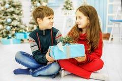 Fröhliche Kinder geben Geschenke Der Junge und das Mädchen Glücklicher Christus lizenzfreies stockbild