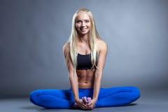 Fröhliche muskulöse blonde Aufstellung in der Lotoslage Stockfotos