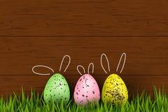 Fröhliche Ostern Buntes, lustiges, nettes Häschen verzierte Wachteln Ostereier, Gras auf hölzernem Hintergrund Designschablone fü Stockfotos