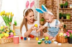 Fröhliche Ostern! Familienmutter und Babysohn malen Eier für Feiertag Stockfoto
