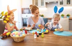 Fröhliche Ostern! Familienmutter und -kinder malen Eier für holida lizenzfreies stockbild