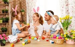 Fröhliche Ostern! Familienmutter, -vater und -kinder malen Eier für lizenzfreies stockbild