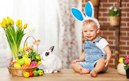 Fröhliche Ostern! glückliches lustiges Baby, das mit Häschen spielt stockfotografie