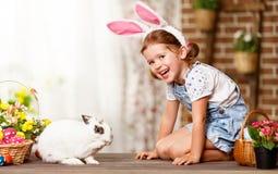 Fröhliche Ostern! glückliches lustiges Kindermädchen, das mit Häschen spielt stockfotografie