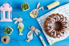 Fröhliche Ostern! Handgemachter Kuchen auf Tuch, Eier, hölzernes Häschen auf blauem hölzernem Hintergrund Dekoration für Ostern lizenzfreies stockbild