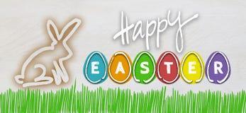 Fröhliche Ostern mit bunten Eiern und Osterhasen auf hellem Holz Lizenzfreies Stockbild