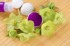 Fröhliche Ostern mit Eierschalen und magentaroter Farbe auf einer gelben Auflage und einem Hellebore Lizenzfreies Stockfoto