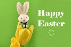 Fröhliche Ostern mit Häschen und gelber Tulpenillustration stockbilder