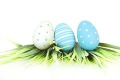 Fröhliche Ostern - wenige Eier auf dem Gras auf dem weißen Hintergrund Lizenzfreie Stockfotografie