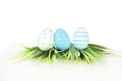 Fröhliche Ostern - wenige Eier auf dem Gras, auf dem weißen Hintergrund Lizenzfreies Stockbild