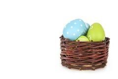 Fröhliche Ostern - wenige Eier auf dem hölzernen Korb auf dem weißen Hintergrund Stockbilder