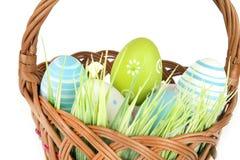 Fröhliche Ostern - wenige Eier auf dem hölzernen Korb mit einem Gras auf dem weißen Hintergrund Lizenzfreie Stockfotos