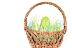 Fröhliche Ostern - wenige Eier auf dem hölzernen Korb mit einem Gras auf dem weißen Hintergrund Lizenzfreies Stockbild