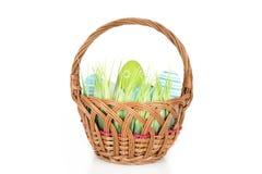 Fröhliche Ostern - wenige Eier auf dem hölzernen Korb mit einem Gras auf dem weißen Hintergrund Stockbild