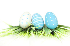 Fröhliche Ostern - wenige Eier mit Gras auf dem weißen Hintergrund Lizenzfreie Stockbilder