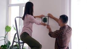 Fröhliche Paare, die das Neu streichen und die Anwendung des Stehleiters für Fallmalerei auf weißer Wand tun stock video footage