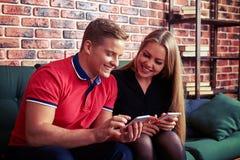 Fröhliche Paare, die wieder auf dem Sofa mit Telefonen in ihrer Hand sitzen Lizenzfreie Stockfotografie