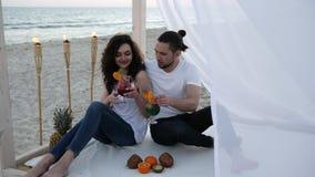 Fröhliche Paare mit Cocktails, haben Spaß, Wind entwickelt weißen Stoff, Bungalow, exotischen Ferien, auf dem tropischen Hintergr stock video footage