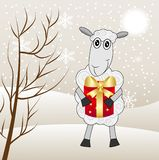 Fröhliche Schafe mit einem Geschenk auf einem Hintergrundwinter gestalten landschaftlich Stockfoto