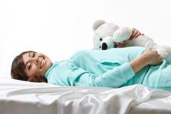 Fröhliche werdende Mutter, die in der Umarmung mit Spielzeug aufwirft Stockfoto