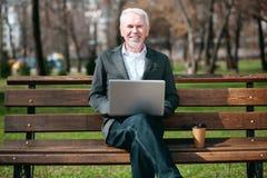 Fröhlicher älterer Geschäftsmann, der an Laptop arbeitet lizenzfreies stockbild