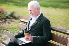 Fröhlicher älterer Geschäftsmannlesebericht lizenzfreie stockbilder