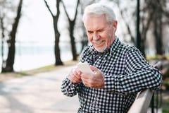 Fröhlicher älterer Mann, der Titelliste wählt lizenzfreie stockfotografie