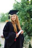 Fröhlicher Absolvent in der Kappe und im Kleid Lizenzfreies Stockfoto