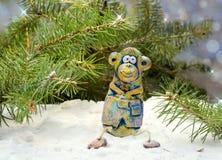 Fröhlicher Affe sitzt unter dem Baum im Schnee Stockfotografie