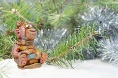 Fröhlicher Affe von den Lehmtonwaren sitzt auf Schlitten nahe dem Baum im Schnee Lizenzfreie Stockbilder