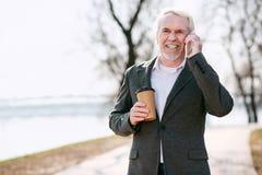 Fröhlicher reifer Geschäftsmann, der Telefongespräch hat lizenzfreies stockbild