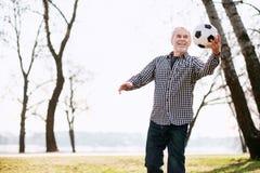 Fröhlicher reifer Mann, der mit Ball trainiert stockbilder