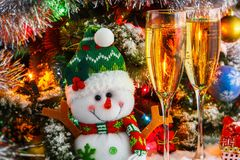 Fröhlicher Schneemann und Weingläser mit Sekt auf dem Hintergrund eines Weihnachtsbaums Lizenzfreie Stockbilder