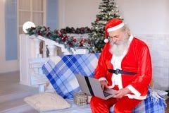 Fröhlicher Vater Christmas, das mit Video durch Laptop spricht Stockfoto