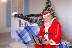 Fröhlicher Vater Christmas, das mit Video durch Laptop spricht Lizenzfreie Stockfotos