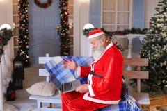 Fröhlicher Vater Christmas, das mit Video durch Laptop spricht Stockbilder