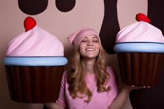 Fröhliches blondes Modell im rosa T-Shirt und in der Kappe, die Spaß mit großem c hat Stockfotografie