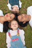 Fröhliches Familienschlafenlügen auf dem Gras Lizenzfreie Stockfotos