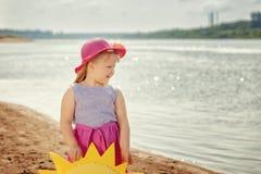 Fröhliches kleines Mädchen, das auf Flussbank, Nahaufnahme aufwirft Stockfotografie