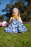 Fröhliches schönes Mädchen, das auf grünem Gras sitzt Lizenzfreies Stockfoto