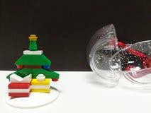 Fröhliches Weihnachten und guten Rutsch ins Neue Jahr, bunter Weihnachtsbaum und kleine Geschenkbox spielen Dekoration mit geöffn Stockfotografie