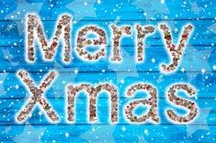 Fröhliches Weihnachten wünscht auf blauem hölzernem Hintergrund und Collage Stockfotografie