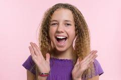 Fröjd, lycka, glädje, seger, framgång och lycka Tonårig flicka på en rosa bakgrund Ansiktsuttryck- och folksinnesrörelsebegrepp fotografering för bildbyråer