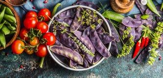 Fröskidor för purpurfärgad ärta i metall bowlar med tomater och matlagningingredienser, bästa sikt royaltyfri fotografi
