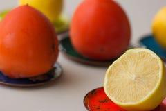 Früchte auf mehrfarbigen dicken Kupferblechen: Persimonen, Zitronen Feijoa-Weißhintergrund Persimone frische Frucht der Zitrone Stockfotos