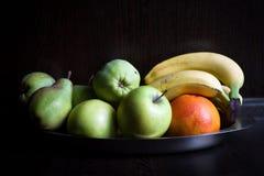 Früchte an der dunklen hölzernen Küche Stockfoto
