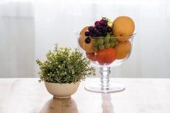 Früchte in der Glasschüssel auf Holztisch Lizenzfreie Stockbilder