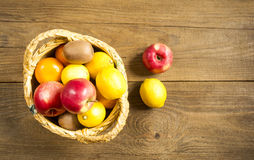 Früchte in einem Weidenkorb auf dem Holztisch Stockfotografie