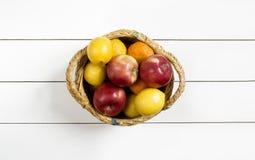 Früchte in einem Weidenkorb auf dem weißen Holztisch Lizenzfreies Stockbild