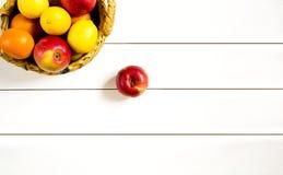 Früchte in einem Weidenkorb auf dem weißen Holztisch Stockfotografie